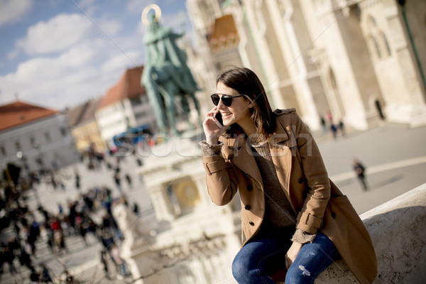 Trendy young woman sitting outdoor and using mobile phone Stock photo © boggy