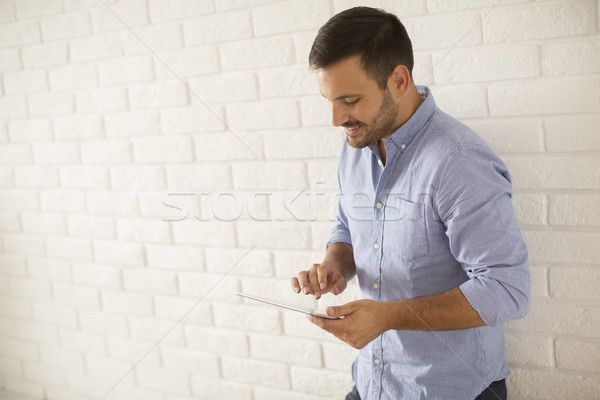 Young man using digital tablet in the room by wall Stock photo © boggy