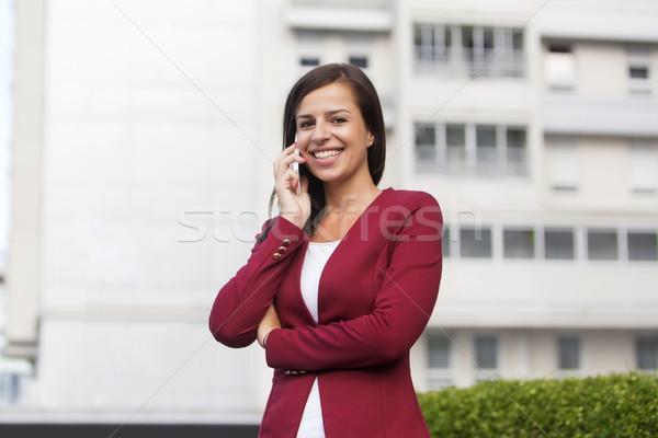 Jeunes femme d'affaires rouge blazer parler téléphone portable Photo stock © boggy