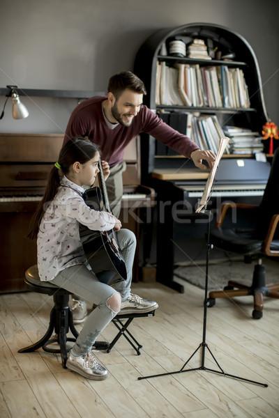 Cute little girl with guitar teacher Stock photo © boggy