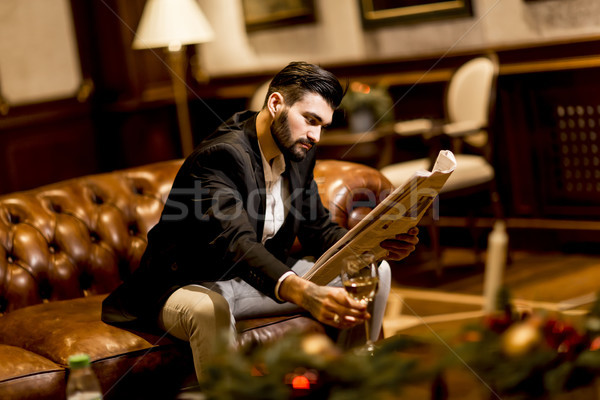 Young businessman drinking wine and reading newspaper Stock photo © boggy