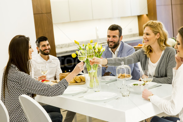 Friends sitting at a dining table celebrating Stock photo © boggy
