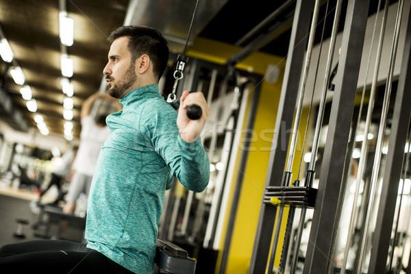 Young man exercise at the gym Stock photo © boggy
