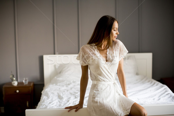 Young beauty girl wake up and sitting on bed at home Stock photo © boggy