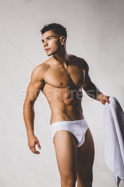 Handsome muscular young man posing in the studio Stock photo © boggy