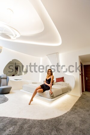 Pretty woman in silk sleeping dress using digital tablet in mode Stock photo © boggy