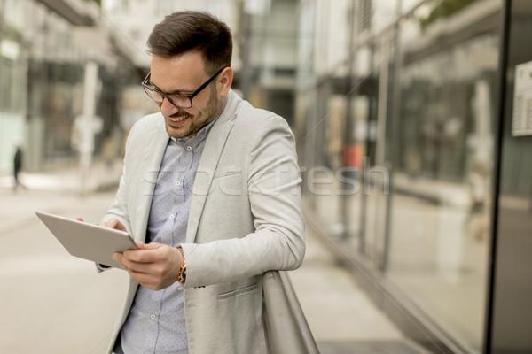 Młodych biznesmen cyfrowe tabletka biurowiec przystojny Zdjęcia stock © boggy