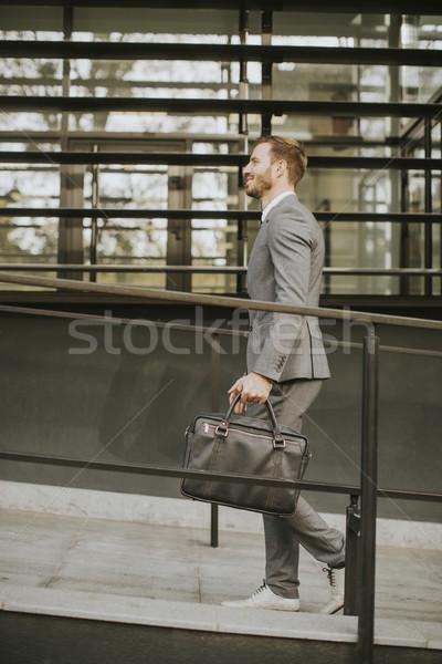 Fiatal jóképű férfi sétál irodaház öltöny tok Stock fotó © boggy