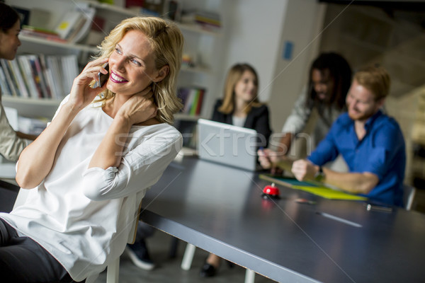 Businesswoman using mobile phone in office and other business pe Stock photo © boggy