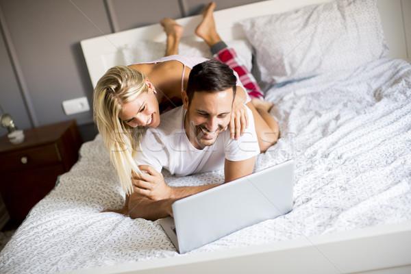 íntimo amantes usando la computadora portátil cama dormitorio sonrisa Foto stock © boggy