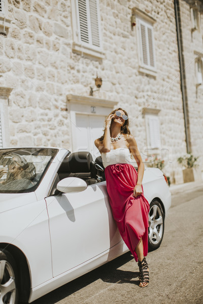 Young attractive woman poses next to a cabriolet at seaside Stock photo © boggy