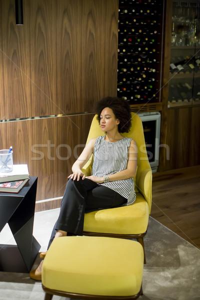 Genç kadın kıvırcık saçlı oturma sarı sandalye görmek Stok fotoğraf © boggy
