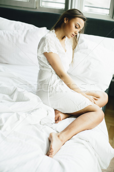 Young woman relaxing in white bed after waking up Stock photo © boggy