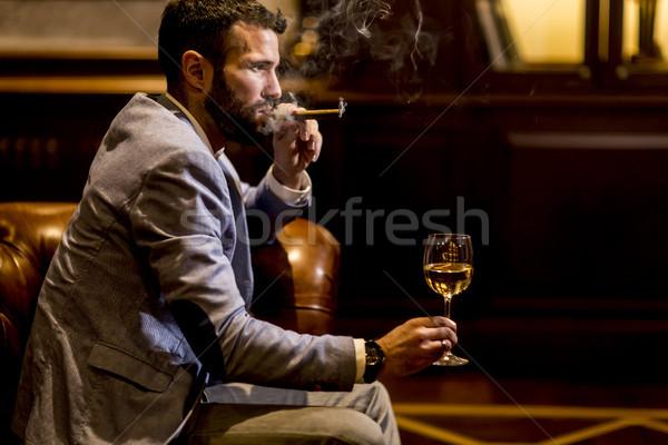 Młody człowiek białe wino palenia cygara wina Zdjęcia stock © boggy