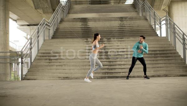 Young woman with trainer exercising in urban enviroment Stock photo © boggy