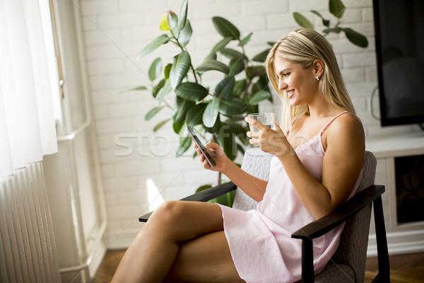 Fiatal nő mobiltelefon tart üveg víz ül Stock fotó © boggy