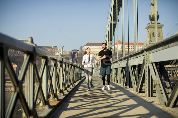 Young couple running in urban enviroment Stock photo © boggy