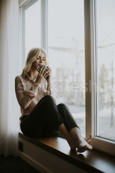 Stock photo: Blonde young woman drinking coffee by window