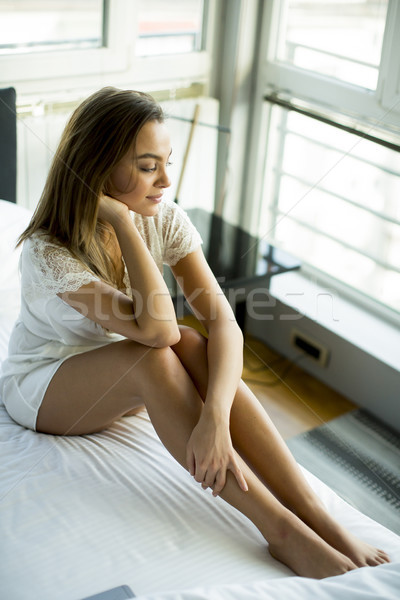 Young woman sitting in bed after waking up Stock photo © boggy