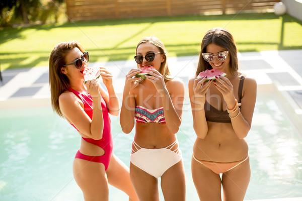 Giovani donne costume da bagno mangiare anguria piscina caldo Foto d'archivio © boggy