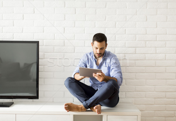 Happy man browsing in a tablet sitting on commode at home Stock photo © boggy