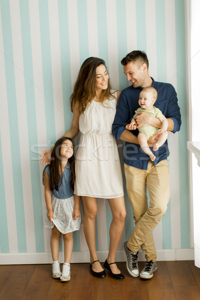Young family with a baby and little girl standing  by the wall Stock photo © boggy