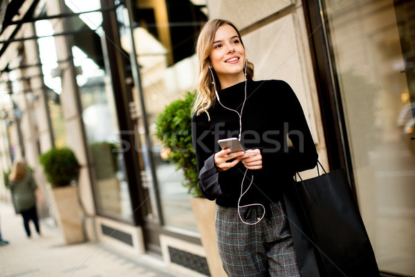 Modern young shopaholic woman on street Stock photo © boggy
