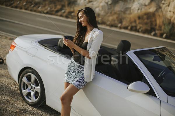 Genç kadın cep telefonu ayakta kabriyole araba sıcak Stok fotoğraf © boggy