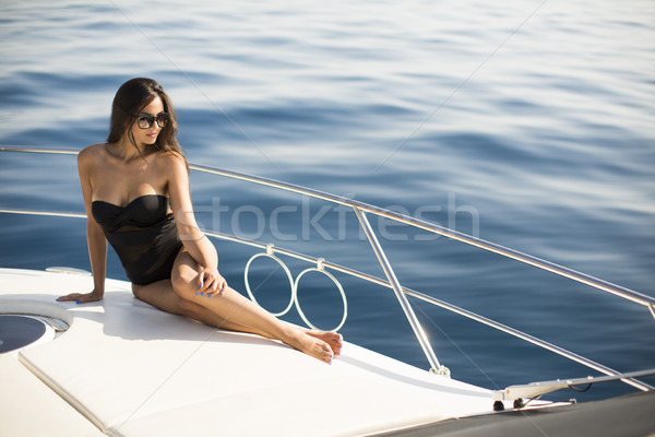 Young attractive woman poses on  luxury yacht floating on sea Stock photo © boggy