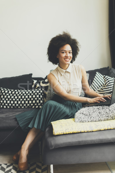 Stock photo: Young woman with curly hair, uses  laptop and sitting on the sof