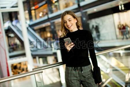 Fiatal nő néz mobiltelefon vásárlás központ portré Stock fotó © boggy