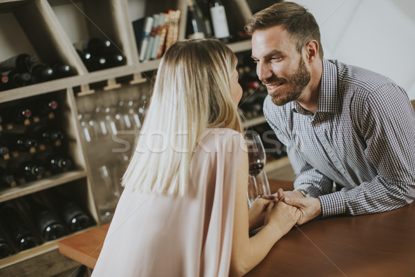 Handsome couple on the date sitting by table in wine bar Stock photo © boggy