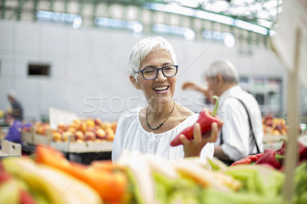 Good-looking senior woman wearing glasses buys pepper on market Stock photo © boggy