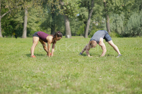 Woman doing stretching exercises with personal trainer in park Stock photo © boggy
