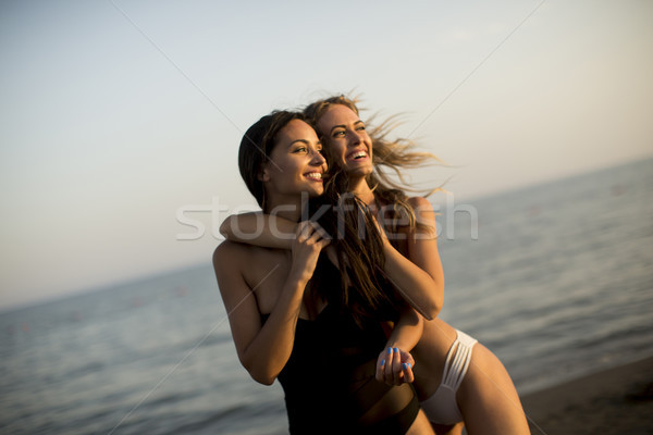 Stock photo: Two young women in swimwear  having fun in the sea at sunset