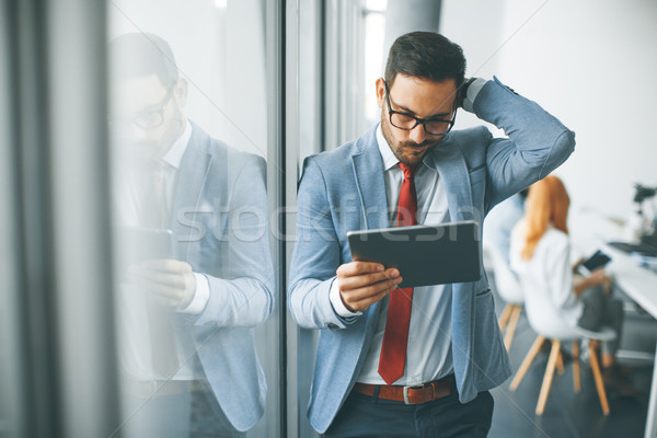 Young businessman with digital tablet in office Stock photo © boggy