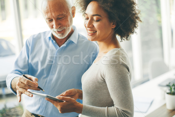 Stock photo: Senior man presenting data to young woman on digital tablet