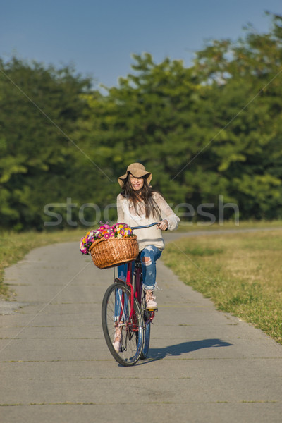 Young smiling woman rides a bicycle with a basket full of flower Stock photo © boggy