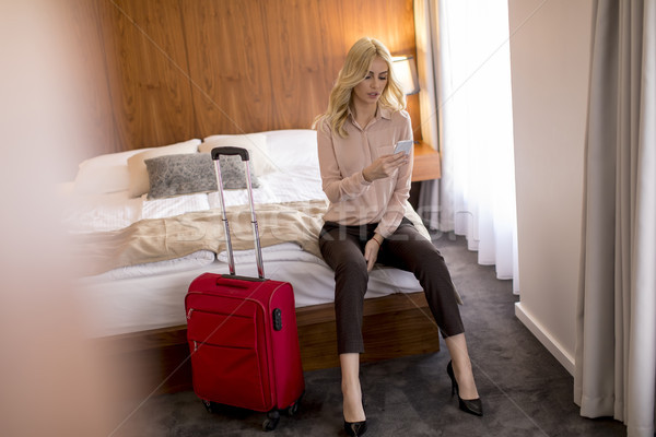 Young businesswoman arrives in a hotel room with red suitcase an Stock photo © boggy