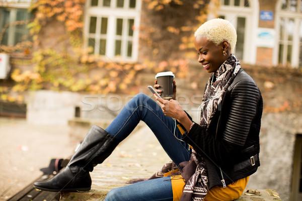 Jovem mulher negra bastante telefone móvel xícara de café mulher Foto stock © boggy
