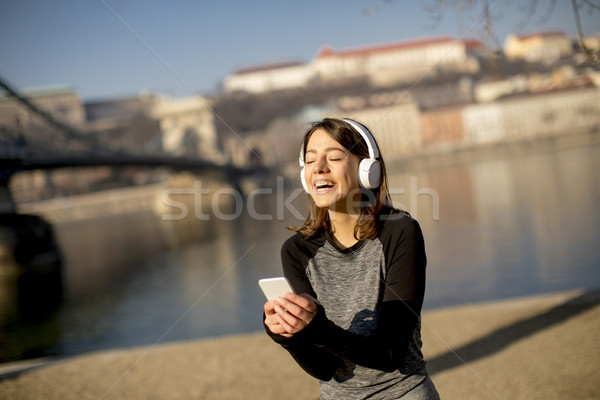 Woman making a pause after the exercise and using mobile phone Stock photo © boggy