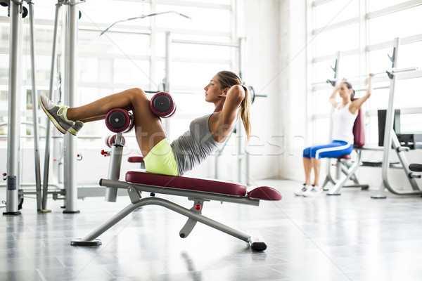 Stock photo: Young woman doing sit-ups in gym