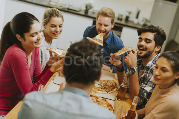 Group of young people eating pizza and drinking cider Stock photo © boggy