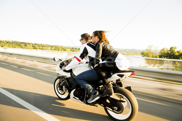 Stock photo: Young couple wearing leather jackets and stylish sunglasses ridi