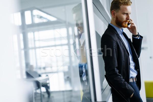 Empresário gengibre cabelo telefone móvel escritório moderno Foto stock © boggy