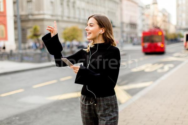 Jonge vrouw wachten taxi bus straat stad Stockfoto © boggy