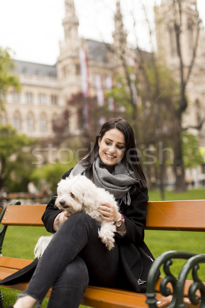 Young woman sitting in the park and holding a small dog in her l Stock photo © boggy