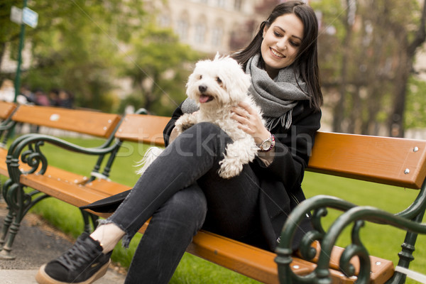 Stock photo: Young woman sitting in the park and holding a small dog in her l