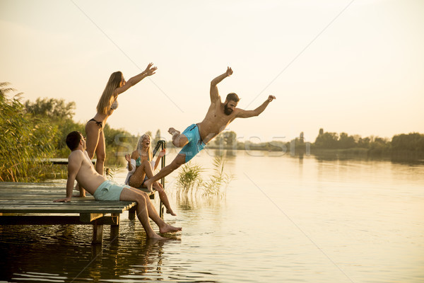 Group of young people having fun on pier at the lake Stock photo © boggy
