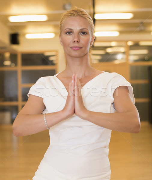 Calm pretty woman doing yoga exercise in studio Stock photo © boggy